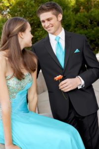 Posing with a prom date in black tuxedo and matching accessories.