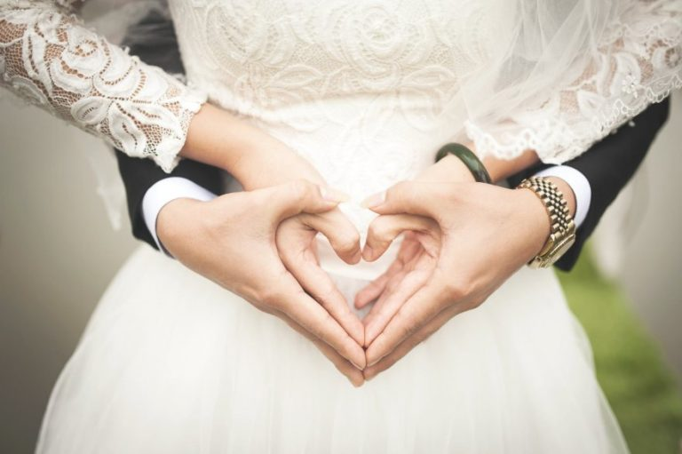 Bride and Groom making hands into a heart shape.