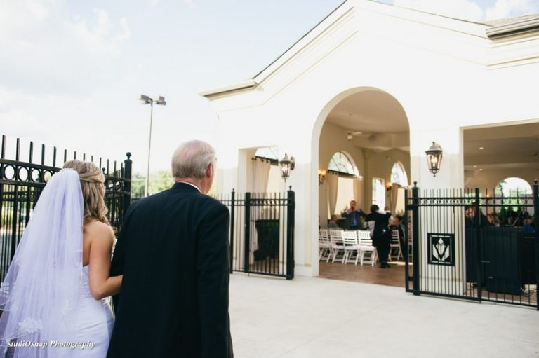 View of the backside of the Bride and Father walking down aisle.