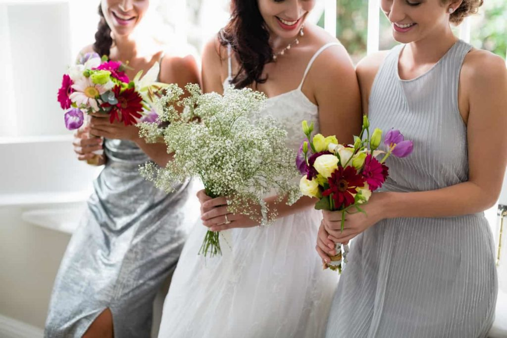 Bride and bridesmaids standing with bouquet at home