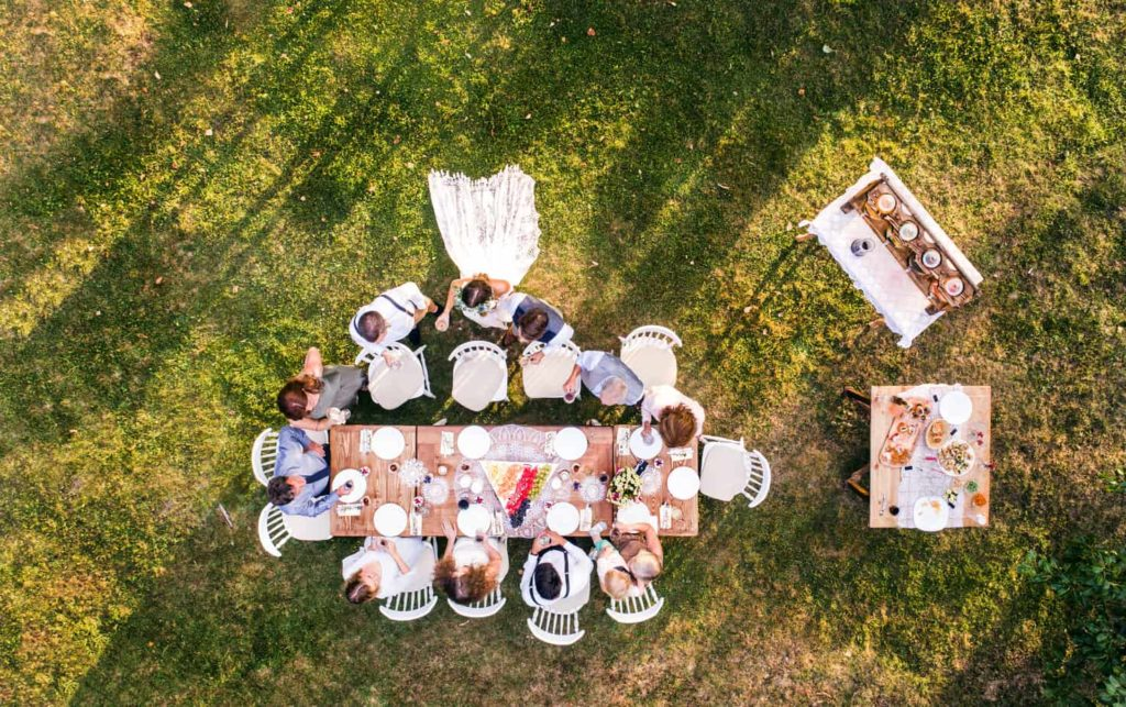 Wedding reception outside in the backyard. Bride and groom with a family standing around the table. Aerial view.