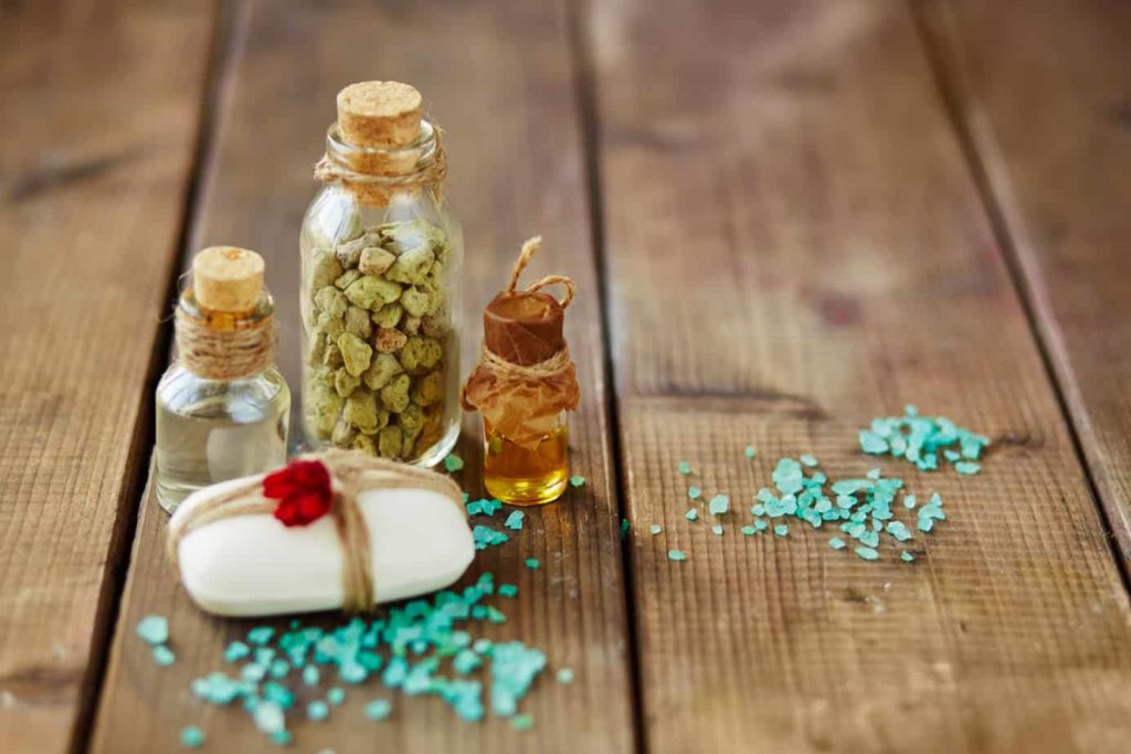 Soap bar bound by thread, sea salt and bottles with spa aromas
