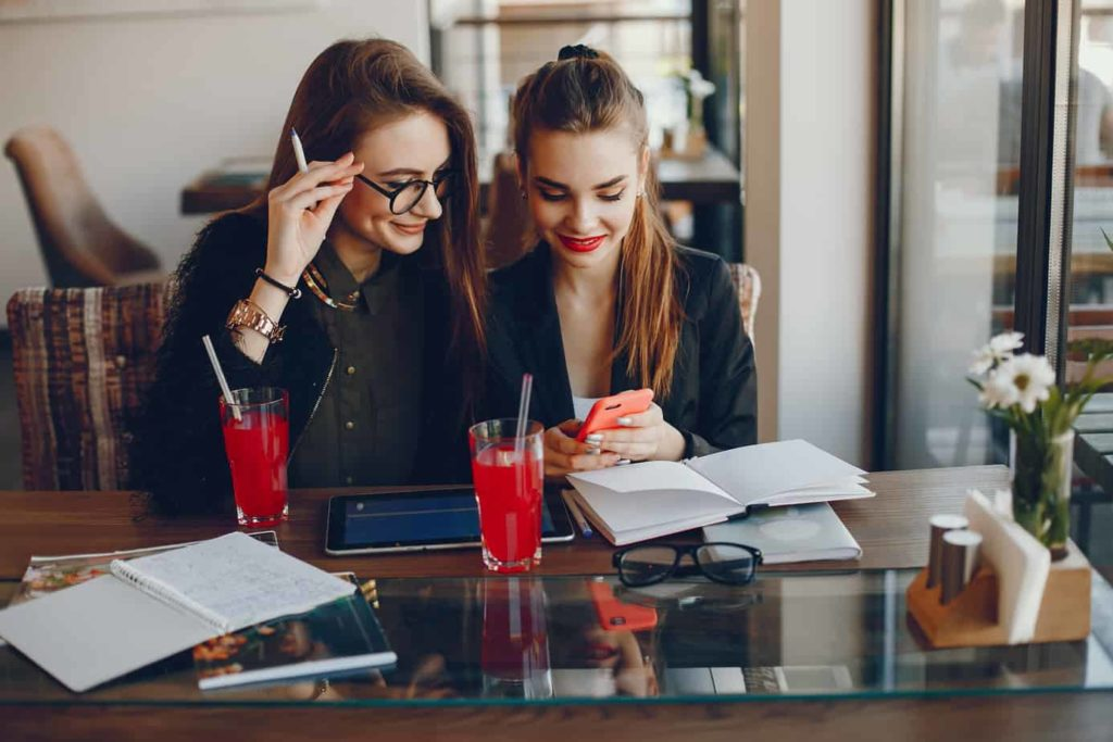 Stylish women sitting at the table. Businesswomen working at the cafe. Girls use the tablet and notebook