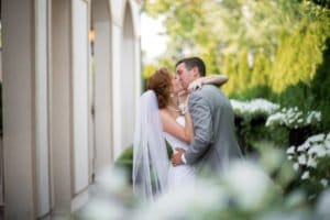 Bride and Groom kissing behind bushes
