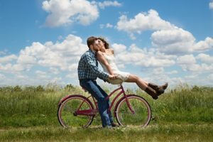 Engagement photos on a bike in a field