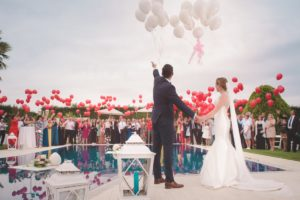 Wedding couple releasing balloons into the sky