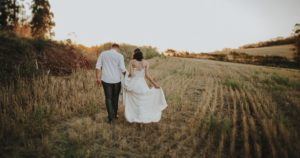 Wedding couple walking through field