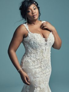 This elegant fit-and-flare wedding dress offers additional coverage. Featuring embroidered lace motifs and crosshatching dance over tulle. Chic lace straps glide from the illusion plunging sweetheart neckline to the scoop back, all accented in beaded lace motifs. Lined with shapewear for a figure-flattering fit. Finished with covered buttons over zipper closure.