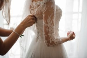Bridesmaid making bow-knot on the back of brides wedding dress